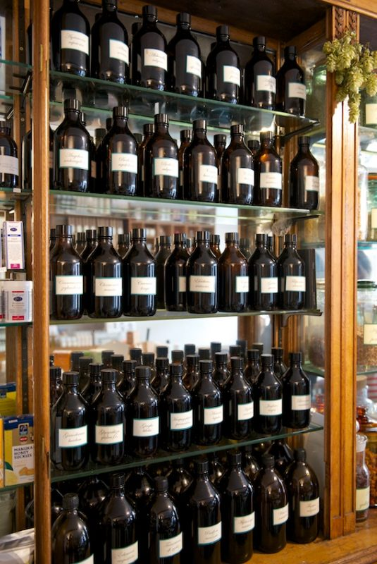 Glass bottles on old chemists' display shelves