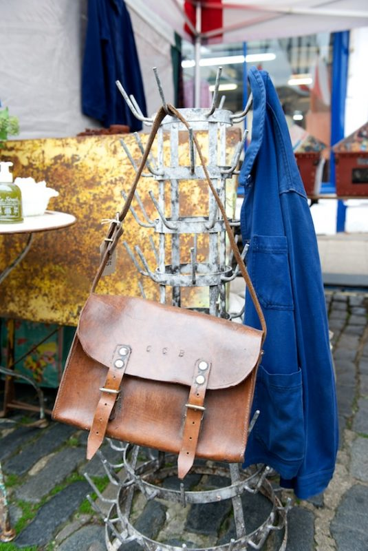 French leather satchel and blue workman's jacket slung on a vintage bottle dryer