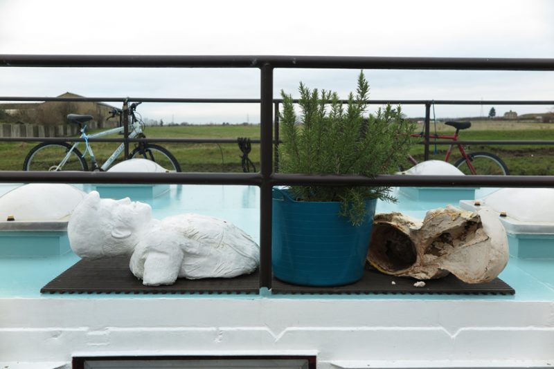 On the deck of a Dutch clipper, now converted to a houseboat at Standard Quay, a rosemary in a plastic trug, flanked by crumbling busts, with the coastal marshes beyond, makes a striking composition