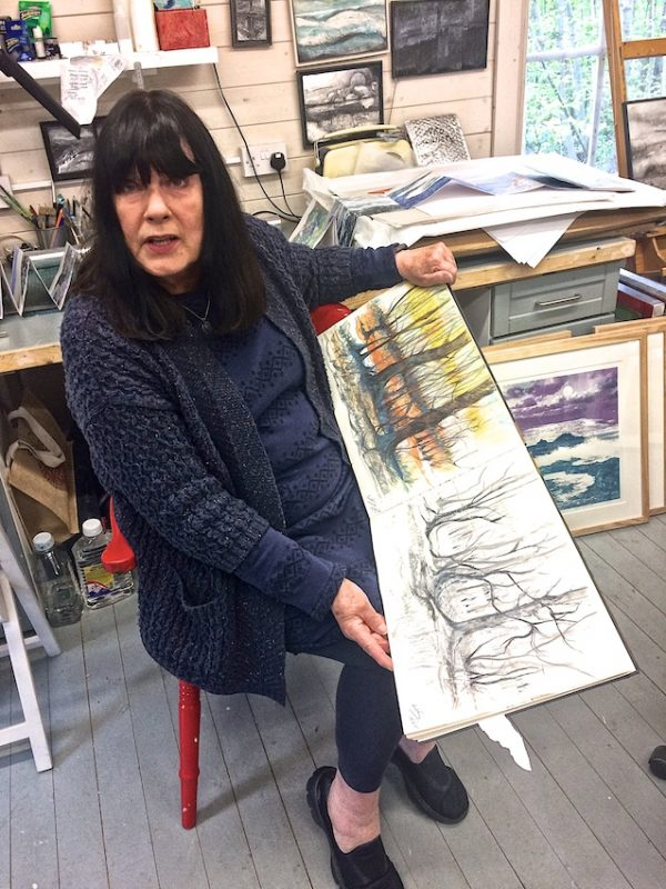 Artist Ruth McDonald in her studio with one of her many sketchbooks.
